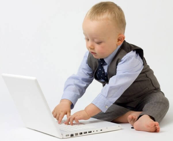 Fotografía de un bebé vestido con traje y chaleco, tecleando en un ordenador portátil, como si fuera un ejecutivo.