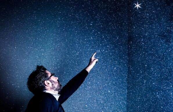 Un hombre, en una habitación empapelada, como si fuera el firmamento por la noche, señalando una estrella que brilla más que el resto.