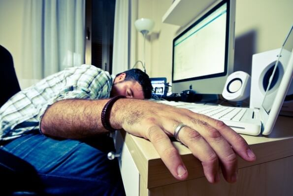 Alguien que ha caído rendido al cansancio, sobre la mesa del despacho frente al ordenador, al no dar abasto con el trabajo.