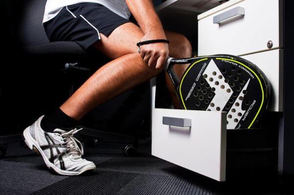 Una persona, vestida con pantalon corto, camiseta y zapatillas de deporte, sacando una raqueta de pádel del cajón del despacho. Sólo se ve poco más que la altura de las rodillas.
