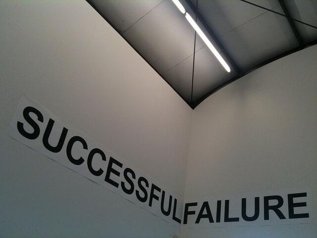 Una fotografía de una esquina de una sala. En una de las paredes que la forman hay un cartel con la palabra successful escrito, éxito. Continua en la otra pared con failure, fallo. Todo junto leído seria un fallo exitoso. Algo parecido al significado de esta entrada, aprender a superar el fracaso para mejorar, y triunfar.