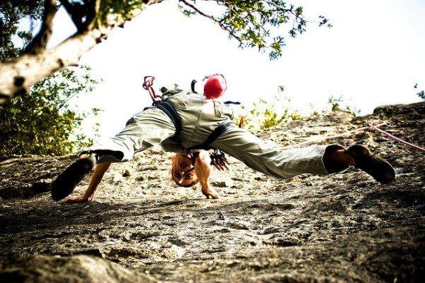 Una fotografía de una persona escalando la pared de una montaña, mirando hacia abajo, como símbolo de persistencia en el camino al éxito.