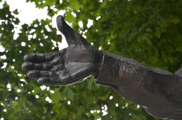 Una mano de bronce, que parece ofrecer su ayuda para resolver los problemas de la humanidad, como haria un buen líder.