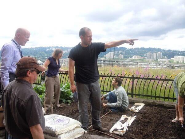 Un grupo de personas plantando un pequeño jardin, y parece que uno de ellos ejerce como lider, e indica a otros que es lo que hay que hacer. Una muestra de que cada día, todos nosotros ejercemos como líderes. Somos líderes anónimos.