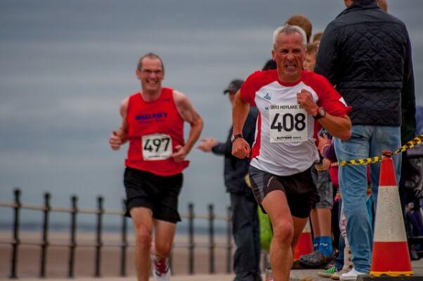 Un primer plano de un hombre empleándose a fondo para continuar corriendo, y conseguir llegar a la meta. Detrás se puede ver otro hombre con gafas con la misma determinación.