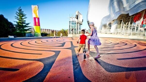 Un par de niños corriendo en una explanada llena de dibujos y colores, cercana al EMP (Experience music project Museum).