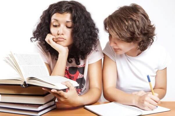 Dos chicas en una mesa con varios libros, y tomando apuntes.