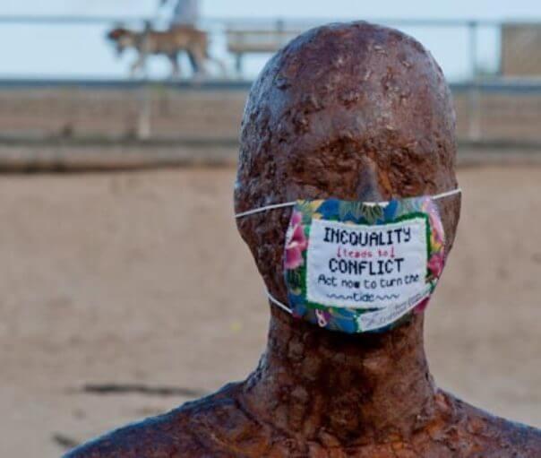 """Una estatua de Antony GormLey, en la que han puesto una máscara como las de los cirujanos. Bordado en la máscara se puede leer """"La desigualdad desemboca en el conflicto, actúa ahora para cambiar el rumbo"""", en inglés."""