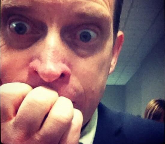Un hombre mordiéndose las uñas, y con los ojos muy abiertos, mostrando una actitud muy nerviosa.