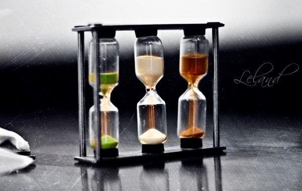 Tres relojes de arena, siendo ésta de diferentes colores dependiendo del reloj, verde, blanca y marrón.