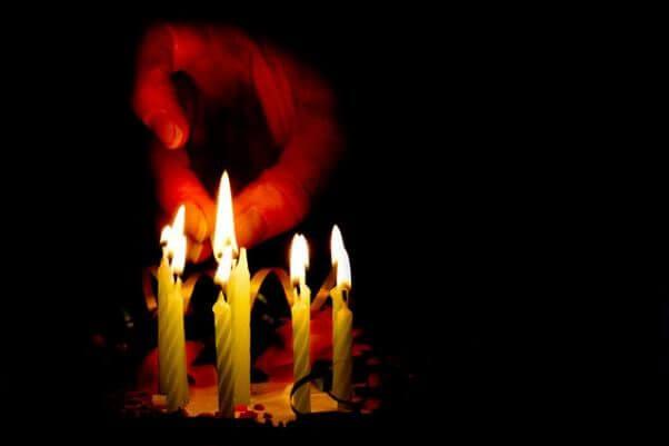 Una mano en la oscuridad, encendiendo las velas de una tarta, para celebrar el cumplemedioaño de Dirección y Liderazgo.