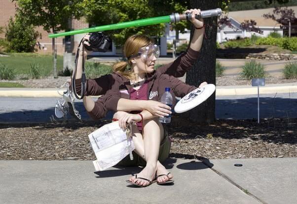 Una chica sentada en la acera, con 6 manos, con las que juega al frisbie, toma una fotografía, sujeta un par de zapatos, una espada láser de juguete, las llaves de casa y un periódico, a la vez que un botellín de agua.