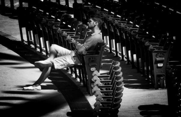 Una persona sentada sola, con decenas de sillas vacías a su alrederor.
