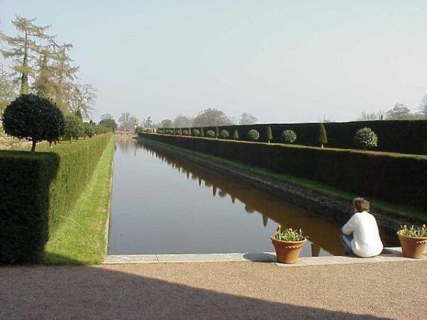 Una persona sentada en un jardín, frente a un estanque de agua. muy probablemente está ordenando sus pensamientos.