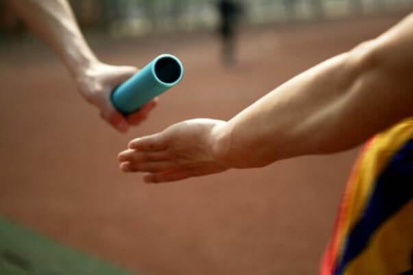 Sólo se ven las manos de dos atletas, pasándose un testigo, en una carrera de relevos.