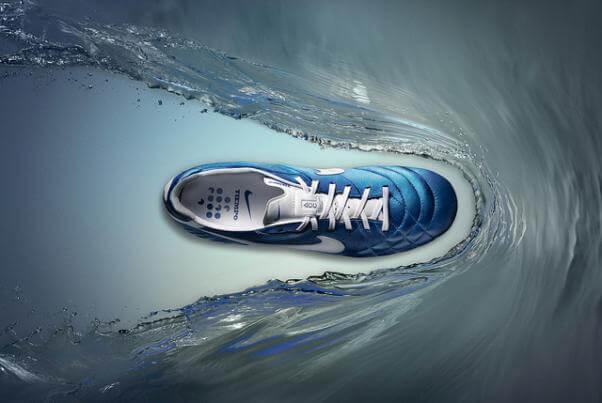 El agua se aparta del camino de unas zapatillas de deporte azules, cuya suela y cordones son blancos.