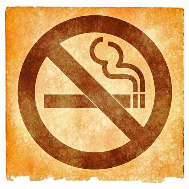 Una señal cuadrada de prohibido fumar, estilo vintage, en colores sepia.