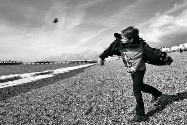 Una persona tirando una piedra al mar. Su rostro muestra ira.