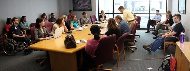 Una fotografía de un equipo, formado por personas muy dispares, en una reunión de trabajo, alrededor de una mesa.