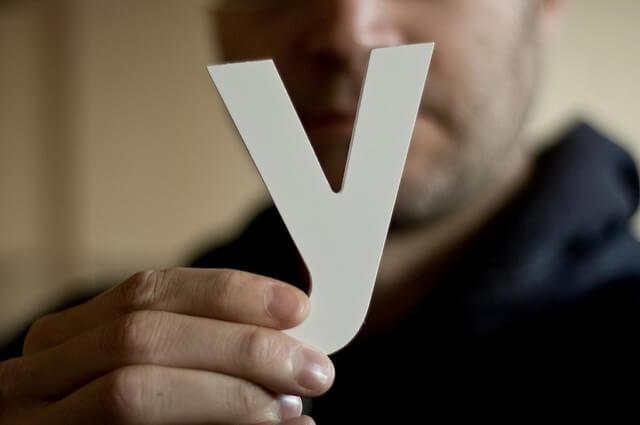 Una letra Y de color blanco, que es sujetada por una personas desenfocada.